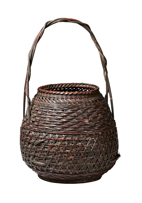 round, bulbous basket with wider bottom; closed weave with a band of overlapping star-shaped pattern in lower half; upper half crisscrossing weave in horizontal pattern; diagonal weave just below mouth; handle made of two crossed slats with a thin reed winding around one of the slats; stands on small foot