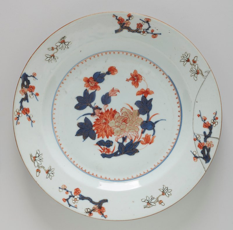 Plate, in center floral spray painted in rose, beige and blue; around rim flowering branches in blue, rose, and white. Bluish white glaze. No marks.