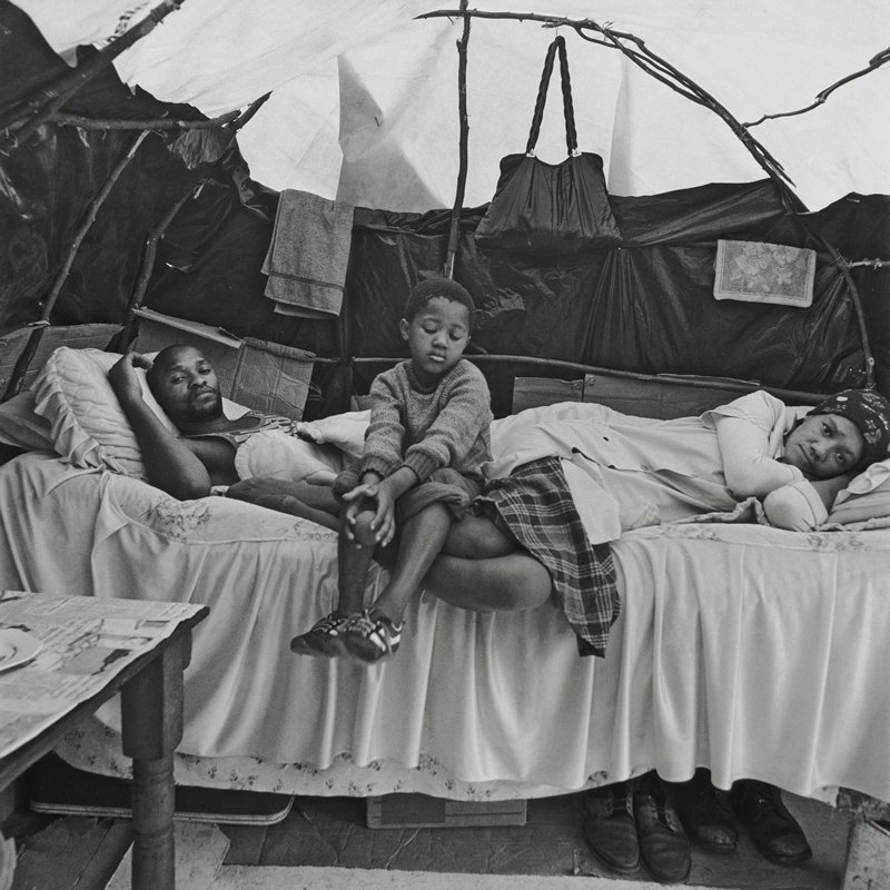 black and white photograph of a man and woman lying down and a seated child child on a bed in a dwelling composed of plastic sheeting and branches