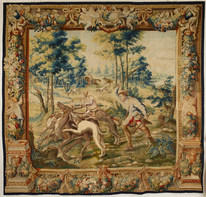 central scene of two hunters with three dogs attacking a stag; other dogs and figures on horseback and running in background; border with figures, putti, flowers, fruit and swags