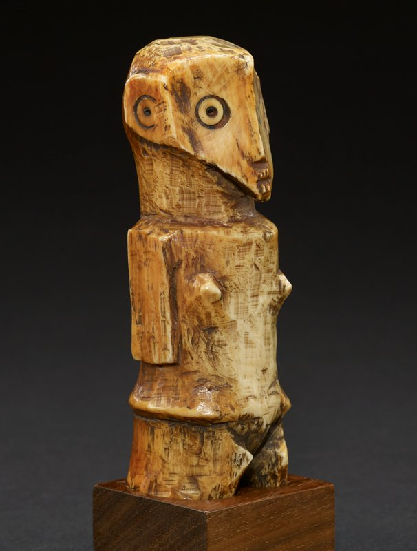 standing figure roughly carved with heart-shaped head and cylindrical body; two protruding mounds indicate breasts and are set wide apart; arms and legs are minimally rendered--no differentiated hands or feet; eyes and ears are wide, simply carved concentric circles; figure's back has series of tiny dark hash marks up and down each side of spine area