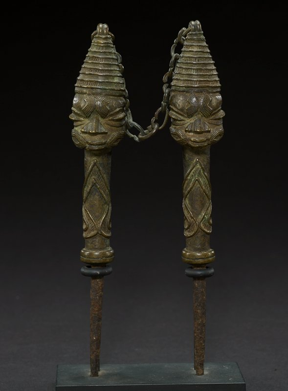 one of two figurative brass staves, which are attached by a chain at the tops of their cone-shaped headdresses; this figure has been identified as female (the other male); however, the staves appear identical, with wide, oval eyes, wide pointed noses, and a small mouth with slightly parted lips; both figures have patterned decoration on their forehead and cheeks; both wear a beehive shaped headdress that ends in a point; the heads are attached to the body of the stave, which has an ornate design; main body of stave is cylindrical in shape, below it the stave leads into a point; staves are all one brass color, with the bottom section appearing to be a more brownish color