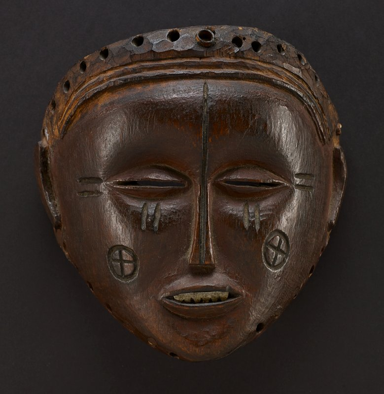 round mask with oval eyes that have narrow horizontal spaces forming eyelids; a thin carved line runs from the top center of the forehead down through the narrow, long nose; the mouth opens to reveal metal teeth; two consecutive indentations mark the sides of both eyes, as well as beneath the eyes; a carved circle with a cross in the middle decorates each cheek; crescent shaped ears protrude slightly on either side of head; a band covers the top of the forehead, with two thin lines followed by a roughly cut layer with some hollowed out holes; entire mask is one natural dark wood color with hints of red, and has sheen to its surface