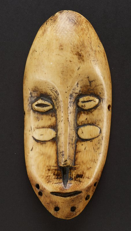 mask is long and oval, with a long narrow nose and two sets of eyes; top eyes each have dark slits that run side to side; bottom eyes are rubbed smooth; there is a deep, vertical groove between the nose and mouth; mouth is small and thin, and below it are six small holes on edge of mask; there is a hole on each side of the mask, at the edge, in between the top and bottom sets of eyes; mask is slightly yellow color of ivory with the carvings appearing brown-black