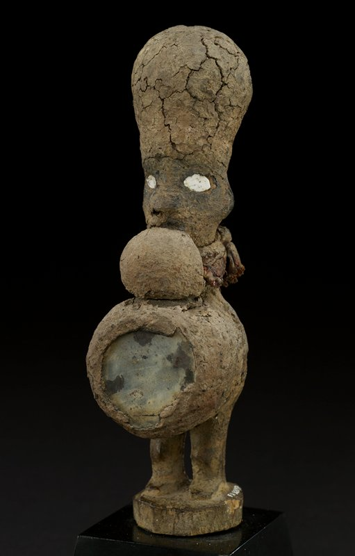standing unisex figure, head adorned with tall, rounded headdress; face is simple with flat, white porcelain eyes, a small carved nose, and a mouth somewhat obscured by round, fabric pouch under chin, which ties at back of neck; figure's abdomen is covered by protruding cylinder with mirrored-front; figure's legs and feet are carved directly into a circular base; overall color of piece is the brown of clay in which it is encrusted; however, there is some red in the fabric piece tied at neck
