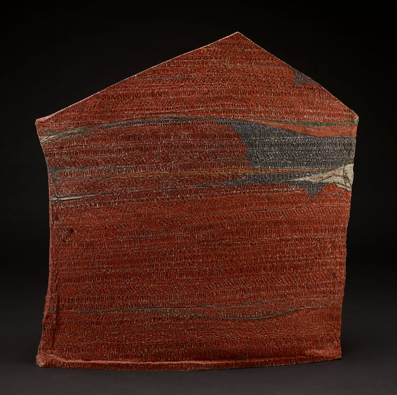 slab-like form; irregular hexagon; slightly convex long sides come to points at edges; two triangular forms at top creating roof-like top face; predominately red with textured horizontal bands with grey, green and brown elements; underside not examined