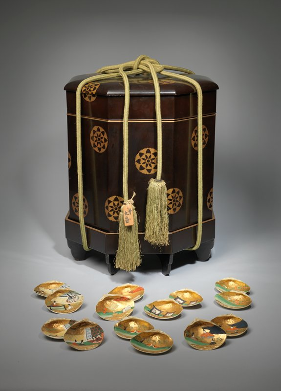 octagonal box in three parts: lid, body, and 8-footed base, with green silk tying cord; black lacquer with stylized floral medallions in gold