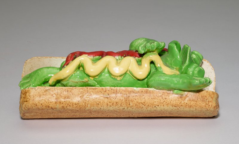 frog stretched out on its back, with ketchup and mustard over its body, lying on a hot dog bun