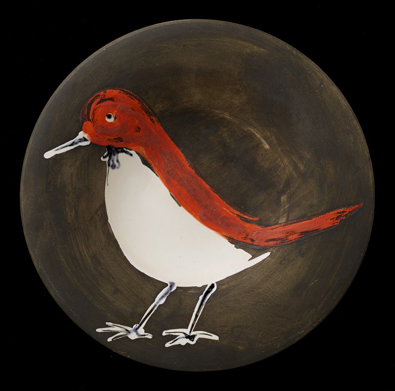 plate with downward-arcing rim; white glaze on bottom; top is matte black with standing red bird with glossy white breast