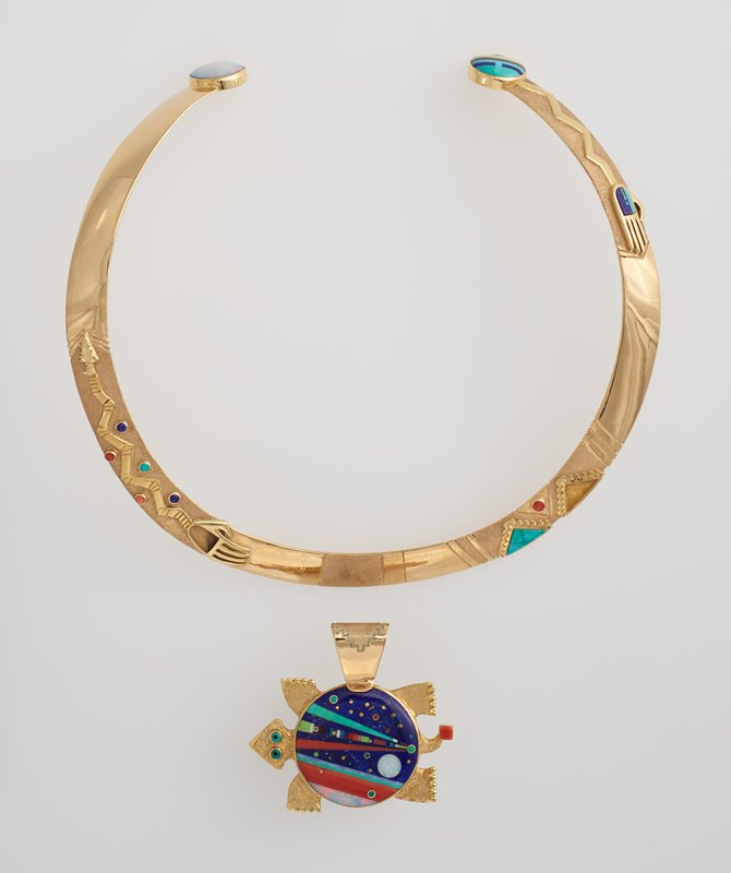 pendant: in the form of a turtle; double-sided; top has coral and turquoise eyes; red coral square at tip of tail; turquoise, lapis and coral beads at points of starburst on shell, with coral gem at center; back has green and black inlaid eyes; red coral square at tip of tail; flat shell on back is inlay in geometric design with dark blue ground with circles, lines and tapering bars in various colors of gemstones; neck collar: curved design, open at back; asymmetrical decoration with hand and arrowhead connected with a zigzag at PR, with inlaid tiny round gems around zigzag; two stepped triangles right of center with turquoise and coral round inlay; hand with predominately blue inlays connected to zigzag at PL near back; ends of collar have inlays--opal on PR, various gems on PL with lines and circles