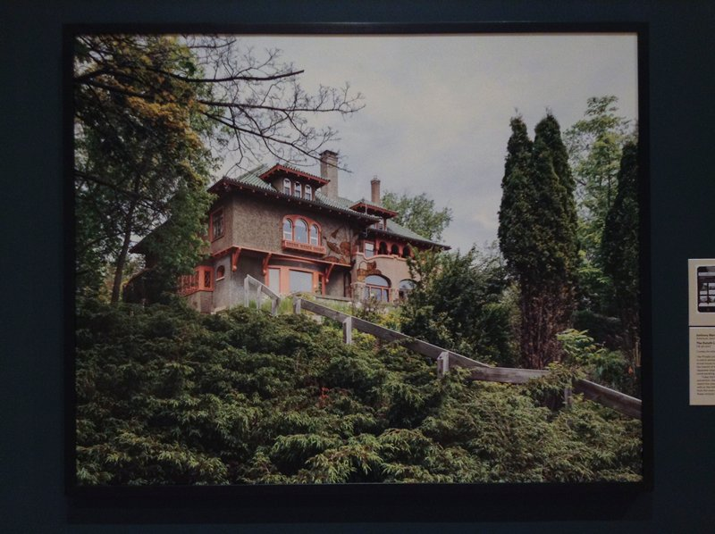 grey house with salmon colored trim and green roof on a hill; dense foliage surrounding a wooden handrail that runs diagonally through the image