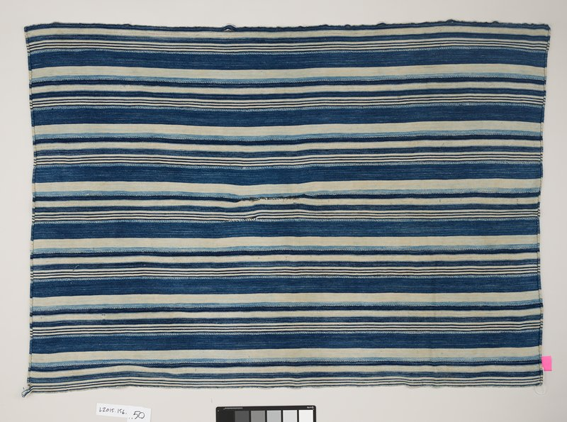 cotton panel with various shades and sizes of blue and white stripes; light blue thread connects 13 strips of fabric together to create panel; two ends are hemmed with blue thread