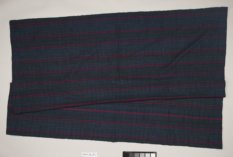 black and blue woven textile with light blue threads speckling throughout the background; red and purple stripes run horizontally; top and bottom of panel are folded and stitched; pale blue edging lines the non-folded sides of the panel