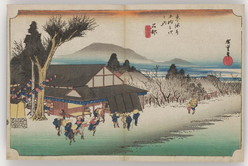 large building with diagonal black screens extending over part of its verandah; on the street, a group of travelers in hats pass by; tree and wall to L of building with colorful banners; another man and a small child walk the thicket-lined path off to the R