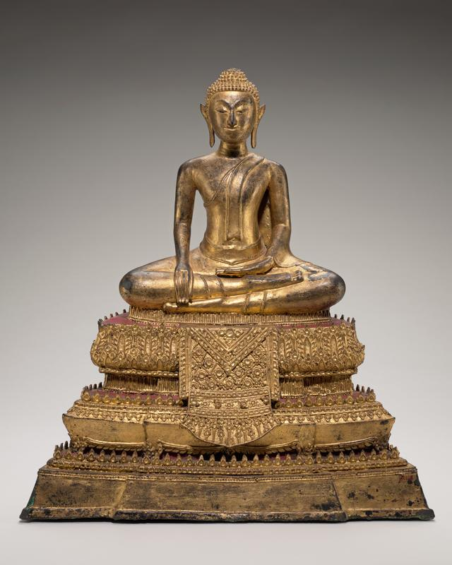 Buddha seated on pedestal; hands rest in lap