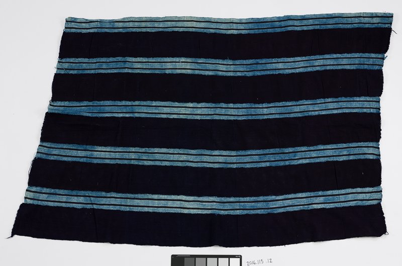 "dark blue strips of cotton alternate lighter blue dyed cotton with two dark strips, 3/8"" in length, overlapping; strips are loosely stitched together with light blue thread; two shorter ends of panel are frayed with raw edges"
