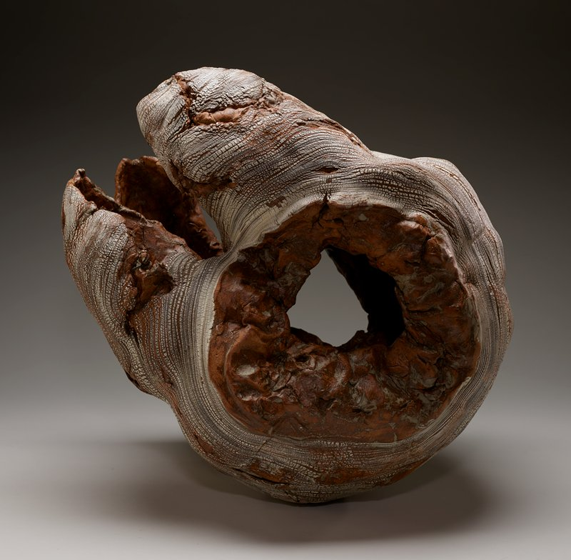 reminiscent of a tree burl; mottled brown and grey at interior and on exterior beneath rows of thick white crackled slip; asymmetrical; round openings at each shorter side with irregular opening at one longer side
