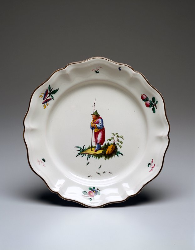 deep faience plate of fluted hexagonal shape; rim edged with green-brown glaze; center of plate contains chinoserie motif of a standing flower with a walking stick; flowers of Indianische Blumen type encircle plate edge; on reverse, two sets of stilt marks visible; colors are blue, yellow and green