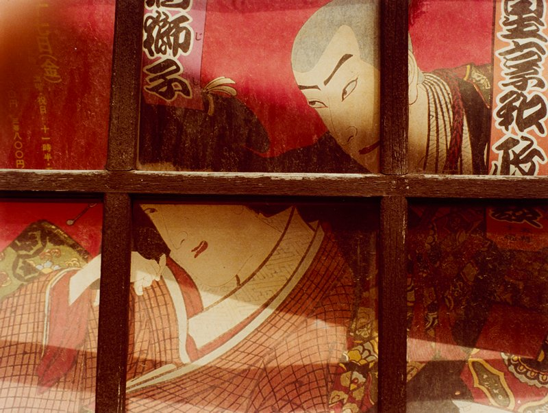 color image of Japanese couple in the style of woodblock printing; red ground; woman wears checked orange kimono; wooden strips in a grid over image