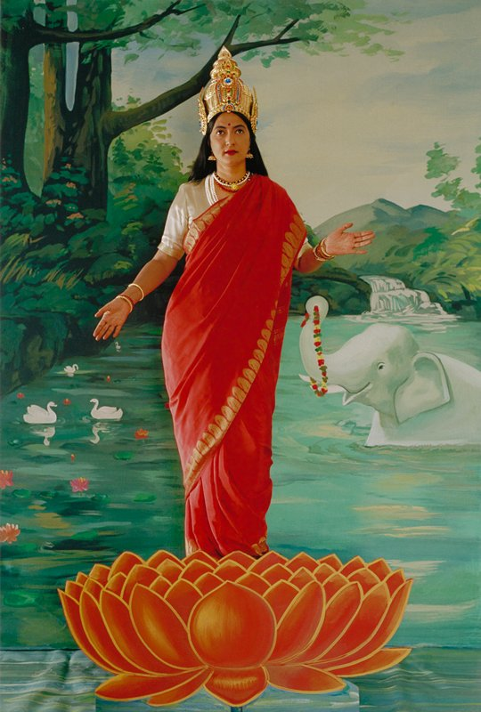 female figure with large golden crown wearing red and white standing on top of a painted red lotus; arms out; painted backdrop with elephant in river, swans, and waterfall