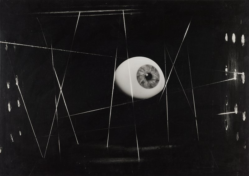 black and white image of an eyeball amidst crisscrossing strings; black background; white circles at L and R