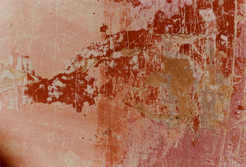 close-up image of a heavily worn, multi-toned red wall or floor with darker red areas, chips, scratches