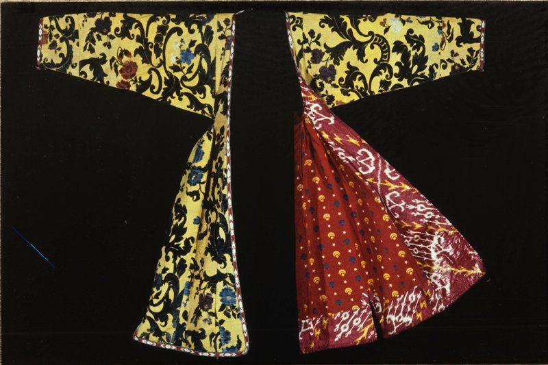 Gentleman's Coat, cloth of gold brocaded with velvet; on the gold background a pattern of velvet leaves in green, and flowers in rose, blue, mauve, and white; facing of cotton print; lining of cotton print, red with yellow crescents and stars. Brought from Moscow by Wannamaker's buyer in 1917. silk, cotton, and gold.