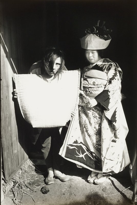 standing woman at right wearing patterned kimono, zori sandals, white tobi socks and hat with looped ribbons; standing crouching figure at left with hair hanging in face, holding a wide, flat basket or mat in front of body