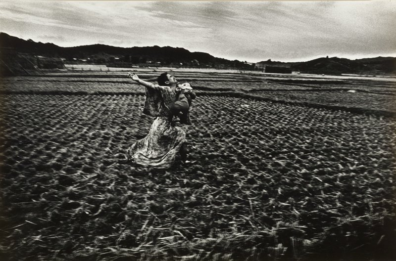 man with PR arm stretched outward behind him, wearing a kimono, running through a plowed field holding a crying baby in his PL arm; mountains in background