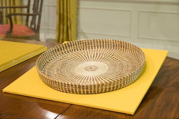 large shallow round woven circular basket; alternating woven bands of grass in light and darker shades of tan; circular pattern in center