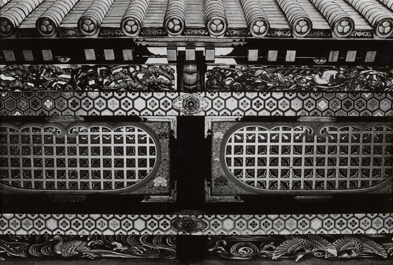 close-up black and white photograph of ornate entrance gate to a shrine; roof tiles along top capped with crests of three leaves; ornately carved lintel with leaves, birds above band of hexagonal crests with flowers; two shaped grates framed with paintings of peonies above another band of hexagons, and another bar of ornate carving