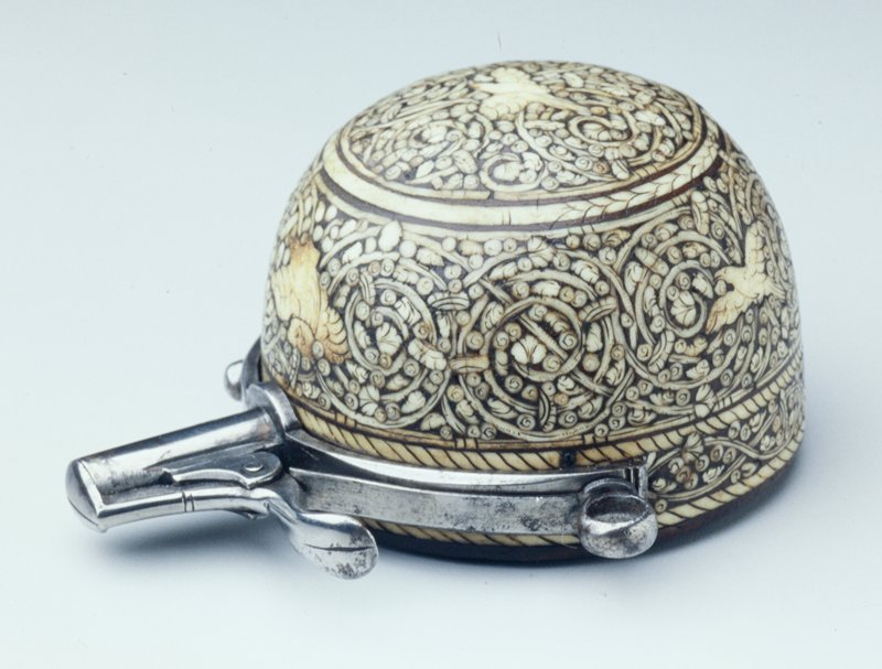 a dome of inlaid bone on wood with attached metal spout with retractable cover, a ring at each side to hang; dome decorated with birds and spiraling vines; flower at center of bottom. Arms and Armor-Accessory