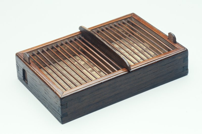 rectangular wood box with bamboo barred cover, 2 wood vertically sliding doors at opposite corners and wood central divider