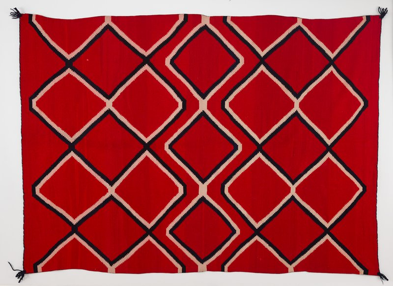 red background; connected diamond patterns of zigzagging double lines in black and white; black tassels at corners; has Velcro heading band