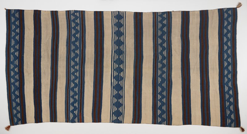 wool panel with cream, blue and brown dyed bands of color in horizontal stripes; blue bands have cream colored geometric design in the form of diamond and zig zag patterns; brown and cream dyed fringe in all four corners; thin border of cream colored thread on two shorter ends; brown colored threading on two longer ends