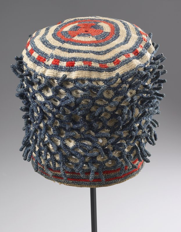 cylindrical shape; ribbed rim with blue, orange and white stripes; overall openwork design in white with short protruding blue tendrils; concentric circles with geometric design at center on top in orange, blue and white; crochet