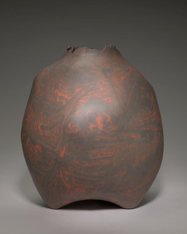 irregular form with smooth, matte surface; marbled orange/brown color; jagged mouth; three feet
