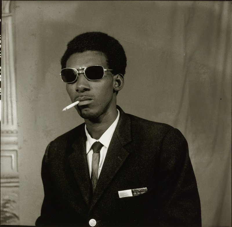 portrait of a black man wearing dark glasses, dark suit jacket and dark tie, with a cigarette in his mouth; card with printed text in man's jacket pocket