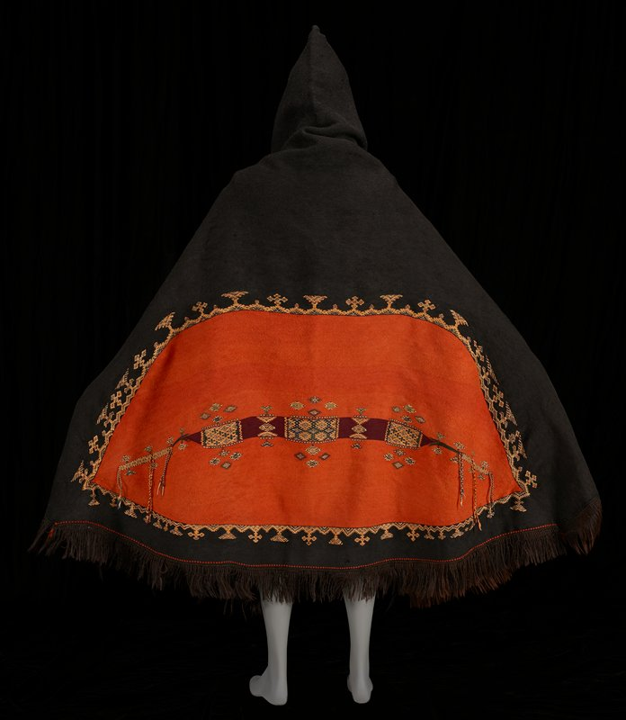large black cape with pointed hood; burnt-orange soft diamond shape on back with maroon band and dark blue, tan, and maroon ikat designs; geometric border separating orange from black; hair-like fringe; small metal rings attached for hanging