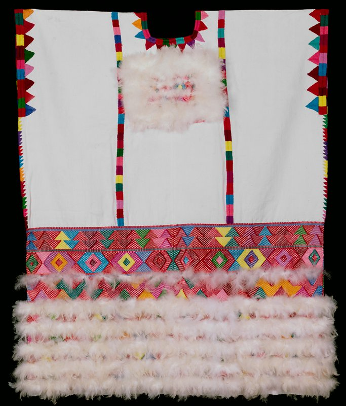 white fabric shirt without sleeves; decorated with wide embroidered trim at bottom edge in multicolored geometric designs; bars of multicolored embroidered rectangles and triangles at neck, chest and sides; feathers at chest and bottom edge