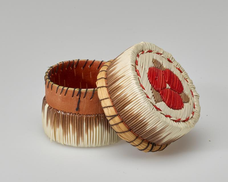 small round box with flat top and bottom; quills overall with white fading into brown on sides; top decorated with red flower with white center and three brown leaves