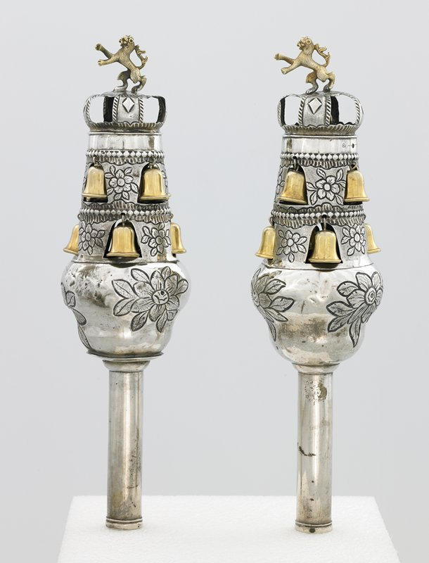 crown-like top section with rearing gold lion at top; silver bell inside crown and 2 rows of 4 gold bells each below; bells hang inside bell-shaped openings; incised flowers between bells and on bottom section
