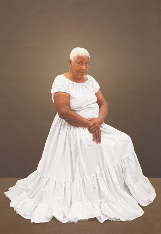 heavy-set elderly dark-skinned woman with short white hair, wearing a long white dress with three gathered tiers, seated, with her hands in her lap, her PL hand holding her PR wrist; grey-brown ground; received framed and unglazed in black poster frame