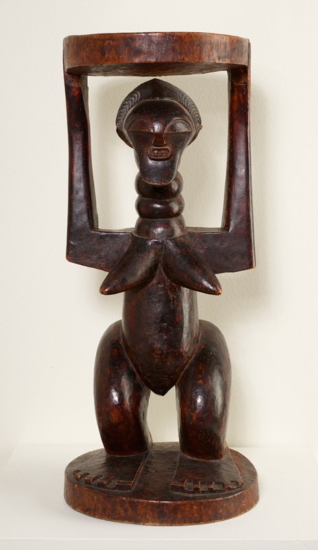 stool with case in the form of a standing woman with her arms upraised, holding seat of stool; woman has abstracted, elongated face with half-circle eyes and oval mouth with regular, gritted teeth; short hair in arcing ribs; lozenge-shaped breasts, pointing outward; elongated neck with four ribs (necklaces?); raised elements (scarifications?) on lower back; thick legs; flat feet with separated toes; medium to dark brown patina