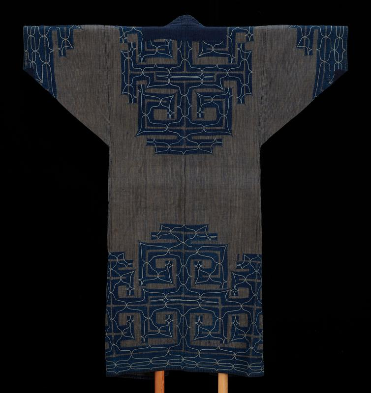 indigo, grey, deep indigo, off-white; deep indigo and grey vertical stripes throughout, except horizontal stripes in triangular lower arm panels; indigo geometric applique at ends of sleeves around collar, upper back and below waist to hem; main applique is formed of slightly curved panels arranged in symmetrical rectilinear angles; off-white curved geometric embroidery line design over applique; flared flaps at waist opening for overlapping when closed; indigo lining throughout interior; small deep indigo hem around front opening and along bottom