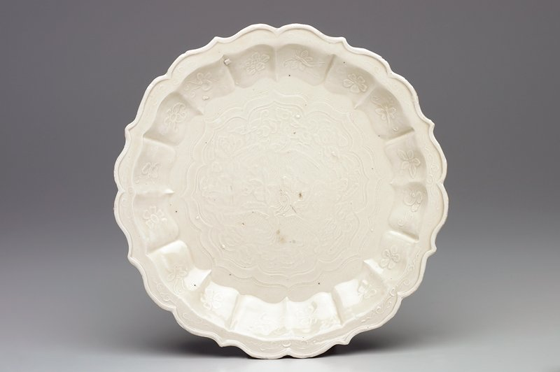 shallow dish with scalloped rim; clear glaze; light raised design of 2 flying birds amid flowers and foliage at center; flowers alternating with insects at rim