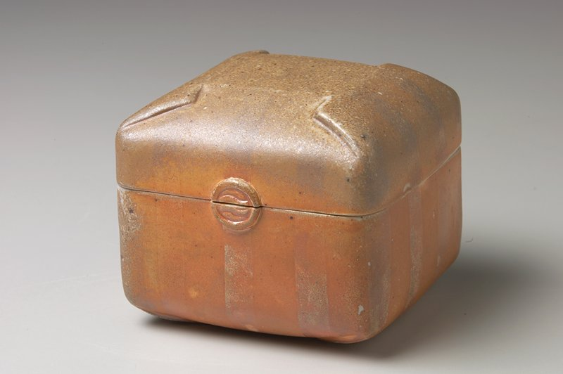 rounded top, bottom and edges resemble folding; applied round element at one side, split by cover and box; light grey glaze on interior; tan and orange on exterior with slip decorated linear pattern