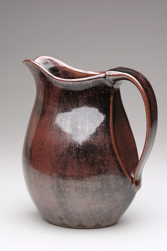 ovoid base with point at center of spout forming a vertical crease; wide applied handle; body of pitcher flat under handle; shiny coppery-brown glaze