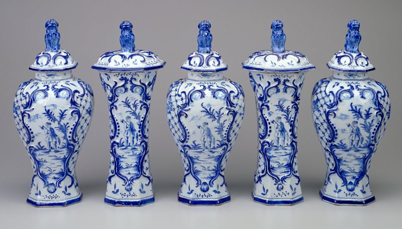 inverted pear-shaped vase with octagonal mouth; domed lid surmounted by dog; wood-cutter next to a tree on front and back inside a Rococo cartouche; flowers and lattice throughout; blue and white