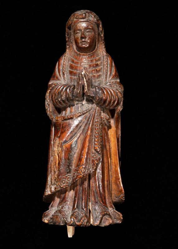 brown patina; standing woman with hands together in prayer; woman wears a headscarf over her shoulders that extends down to her skirt hem in back, with edging of circles between bands; very regular vertical folds in clothing on back